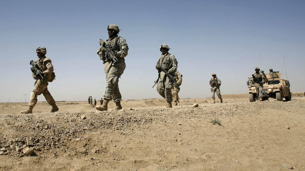 In this file photo, U.S. and Canadian soldiers walk out of a military base during a joint patrol with Afghan police in the town of Howz-E-Madad, some 35 km west of Kandahar, Oct. 10, 2007.