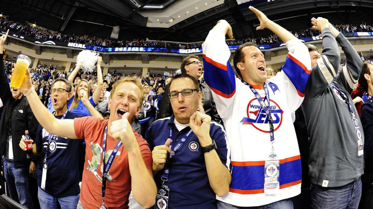 Winnipeg Jets' fans celebrate their team's first goal against the Montreal Canadiens' during the third period of their NHL hockey game in Winnipeg, Manitoba October 9, 2011. The Winnipeg Jets are playing their first season game since the franchise left the city 15 years ago.