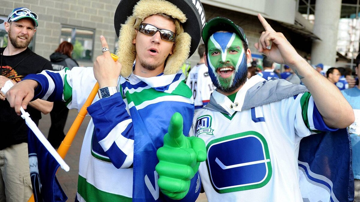 Fans of the Vancouver Canucks pose outside the arena prior to Game 2 between the Vancouver Canucks and the Boston Bruins in the 2011 NHL Stanley Cup Final at Rogers Arena on June 4, 2011 in Vancouver.