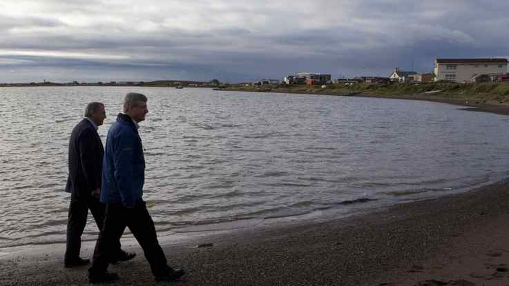 Prime Minister Stephen Harper, right, walks on the shore of the Beaufort Sea with Minister of Indian Affairs and Northern Development John Duncan while they visit Tuktoyaktuk, Northwest Territories on the fourth day of his five day northern tour to Canada's Arctic on Aug. 26, 2010.