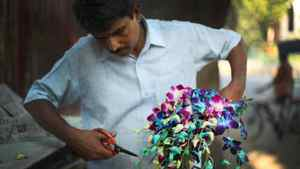During the day, Ayodha Prasad Verma cuts and prepares flowers for a constant rush of customers.