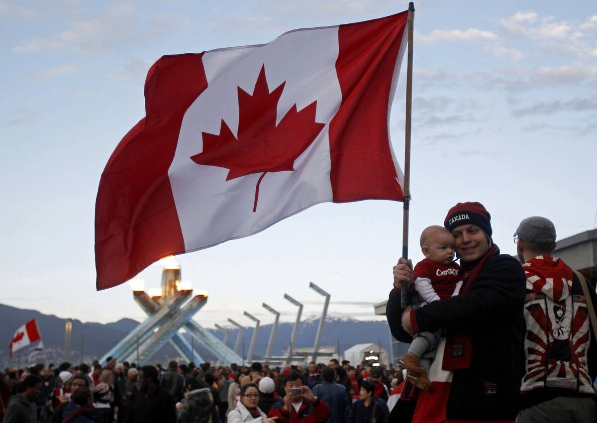 A Canadian mother and her child proudly wave the Maple Leaf in front of the Olympic cauldron after Canada's gold-medal hockey victory over the United States in Vancouver on Feb. 28, 2010.