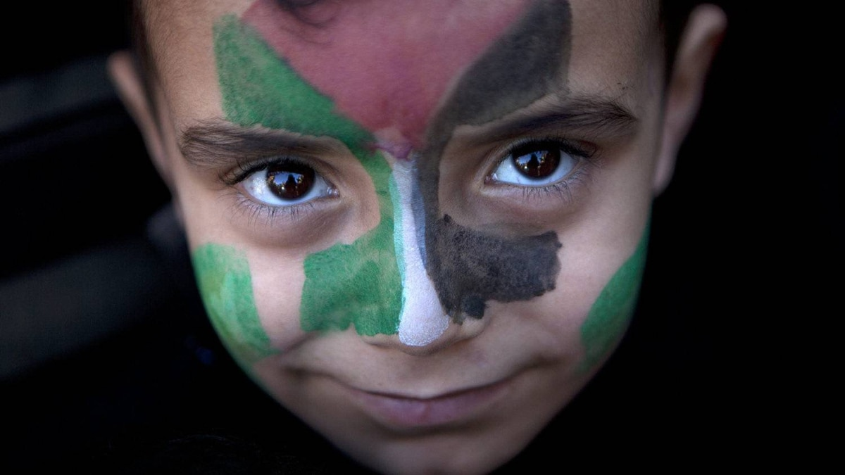 A young Palestinian boy with his face painted the colors of the Palestinian flag during a rally marking the 23rd anniversary of the group's founding in Gaza City on Dec. 14, 2010.