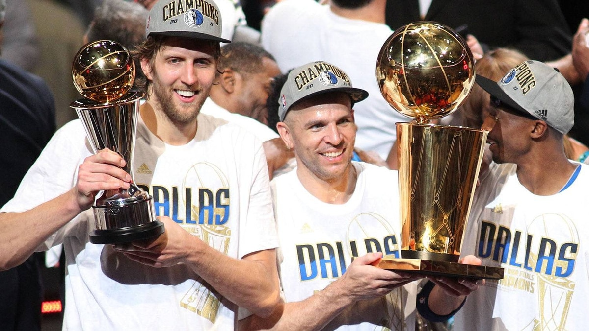 (L-R) Finals MVP Dirk Nowitzki #41, Jason Kidd #2 and Jason Terry #31 of the Dallas Mavericks celebrate with the Larry O'Brien trophy after they won 105-95 against the Miami Heat in Game Six of the 2011 NBA Finals at American Airlines Arena on June 12, 2011 in Miami, Florida. (Photo by Marc Serota/Getty Images)