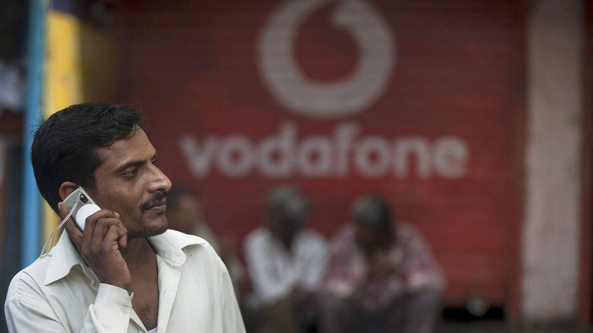 A man speaks on a mobile phone in front of a Vodafone Group Plc. advertisement in Mumbai, India, on Saturday, July 25, 2009.