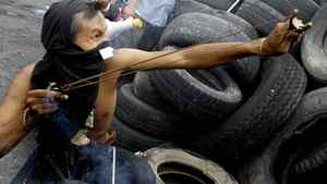 An anti-government protester uses a slingshot against Thai soldiers May 18, 2010 in Bangkok.