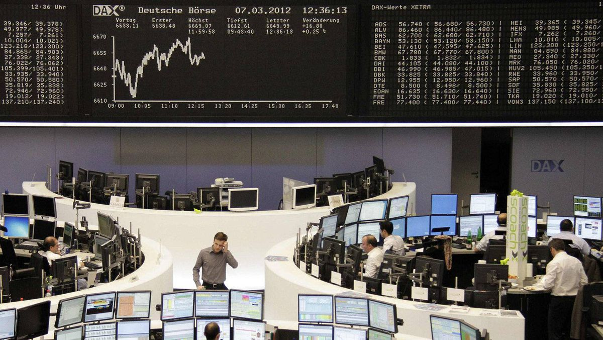 Traders are pictured at their desks in front of the DAX board at the Frankfurt stock exchange March 7, 2012.