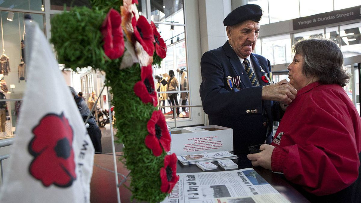 A Royal Canadian Legion member pins a Remembrance Day poppy on a woman's coat at Toronto's Eaton Centre on Nov. 8, 2010.