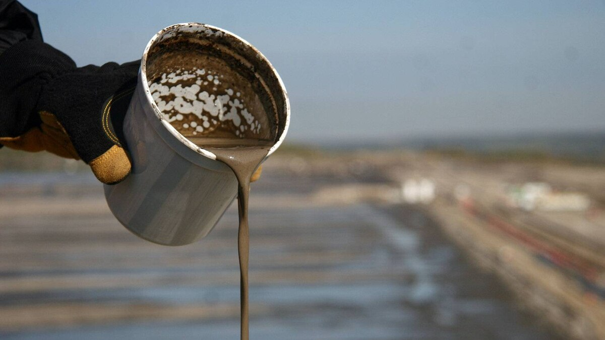 A worker pours oil-sands tailings in front of a new Suncor Energy Inc. cleanup site in Alberta.