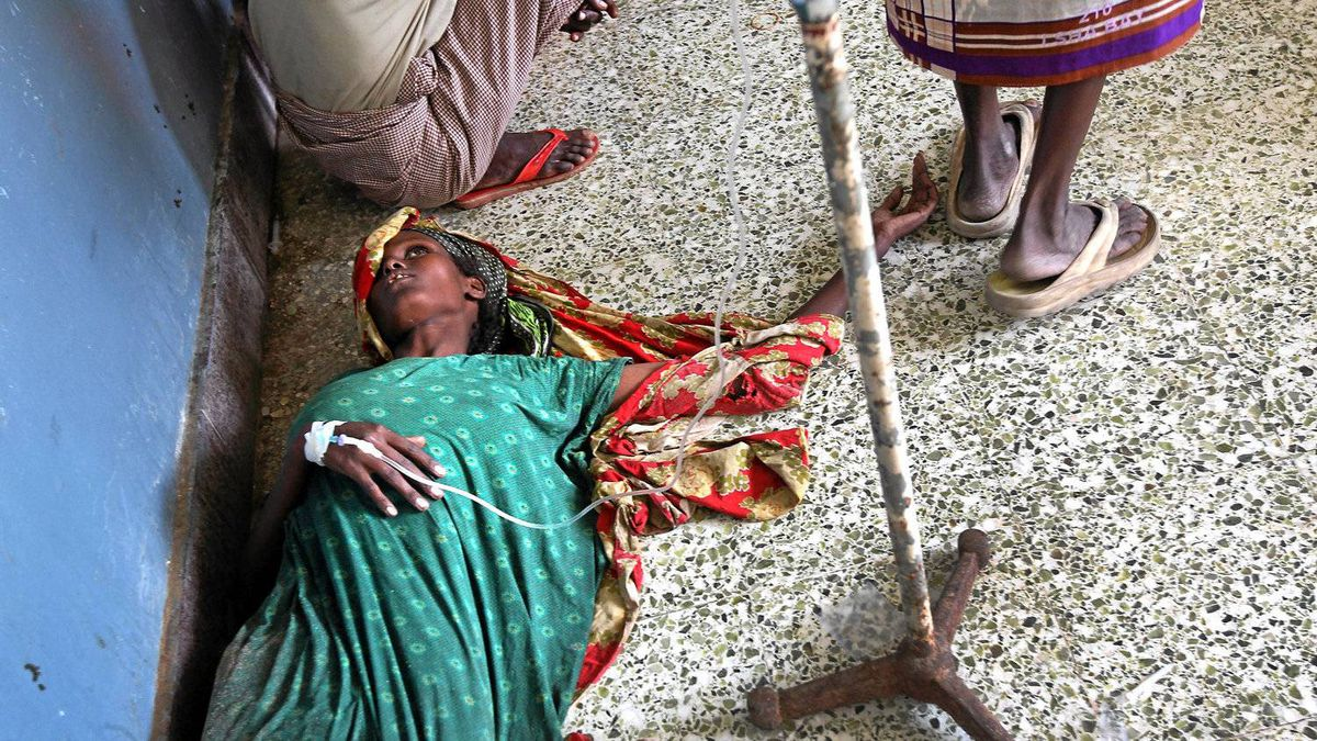 A Somali woman, dehydrated and gaunt from severe diarrhea, lies in a corridor due to lack of bed space at the Banadir hospital on August 14, 2011 in Mogadishu, Somalia.