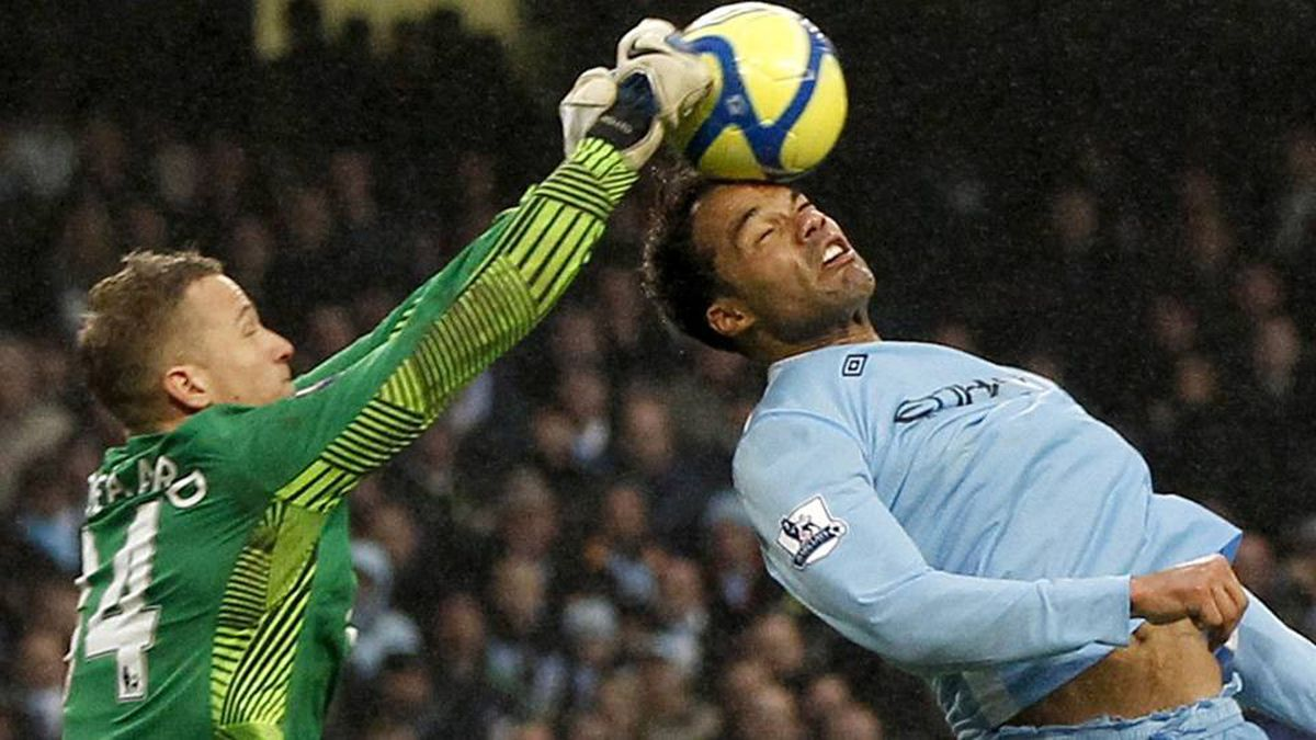Manchester United's Anders Lindegaard, left, clears the ball from the head of Manchester City's Joleon Lescott during their FA Cup soccer match.