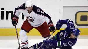 Vancouver Canucks' Henrik Sedin, (33) of Sweden, tries to maintain control of the puck after getting knocked down by Columbus Blue Jackets' Jan Hejda, of the Czech Republic, during the first period of NHL hockey action at GM Place in Vancouver, Friday, February 29, 2008.