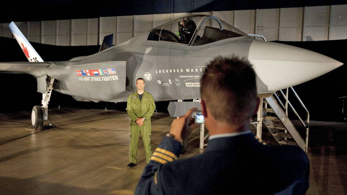 A Canadian Forces pilot has his picture taken in front of a F-35 Joint Strike Fighter prior to a procurement announcement in Ottawa on July 16, 2010.