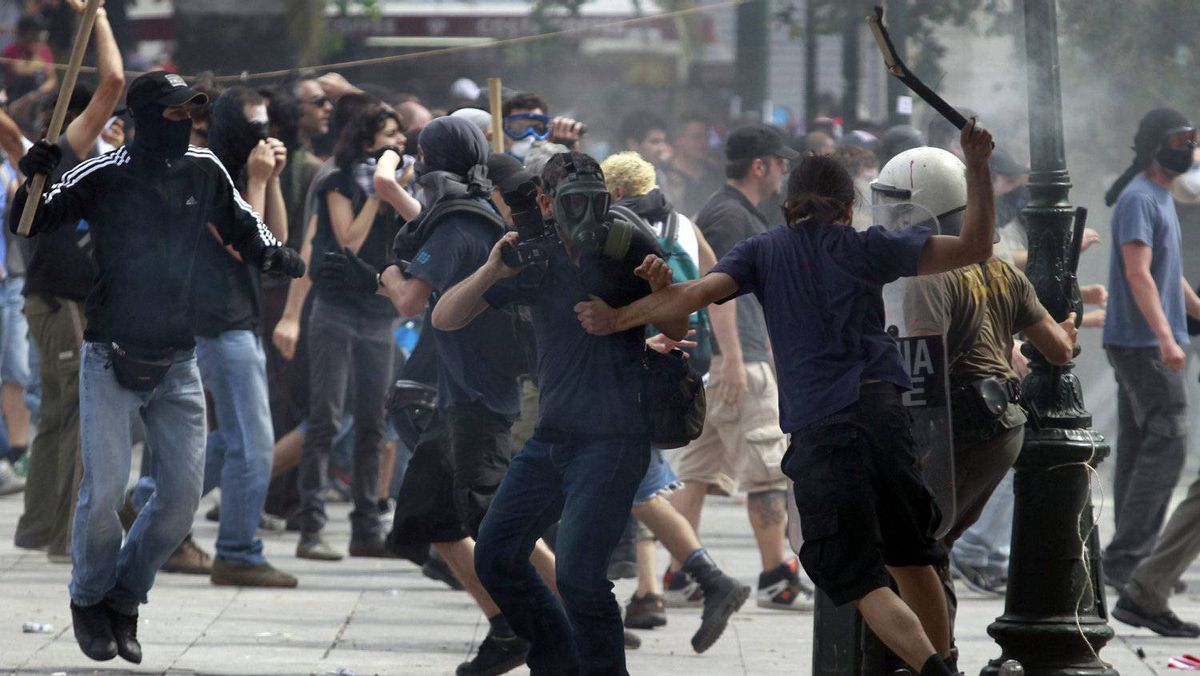 A photographer, center, reacts as Greek protesters run with batons to hit a riot police officer, right, during clashes in Athens' main Syntagma square, Wednesday, June 15, 2011. Hundreds of protesters clashed with riot police in central Athens Wednesday as a major anti-austerity rally degenerated into violence outside Parliament, where the struggling government was to seek support for new cutbacks to avoid a disastrous default.