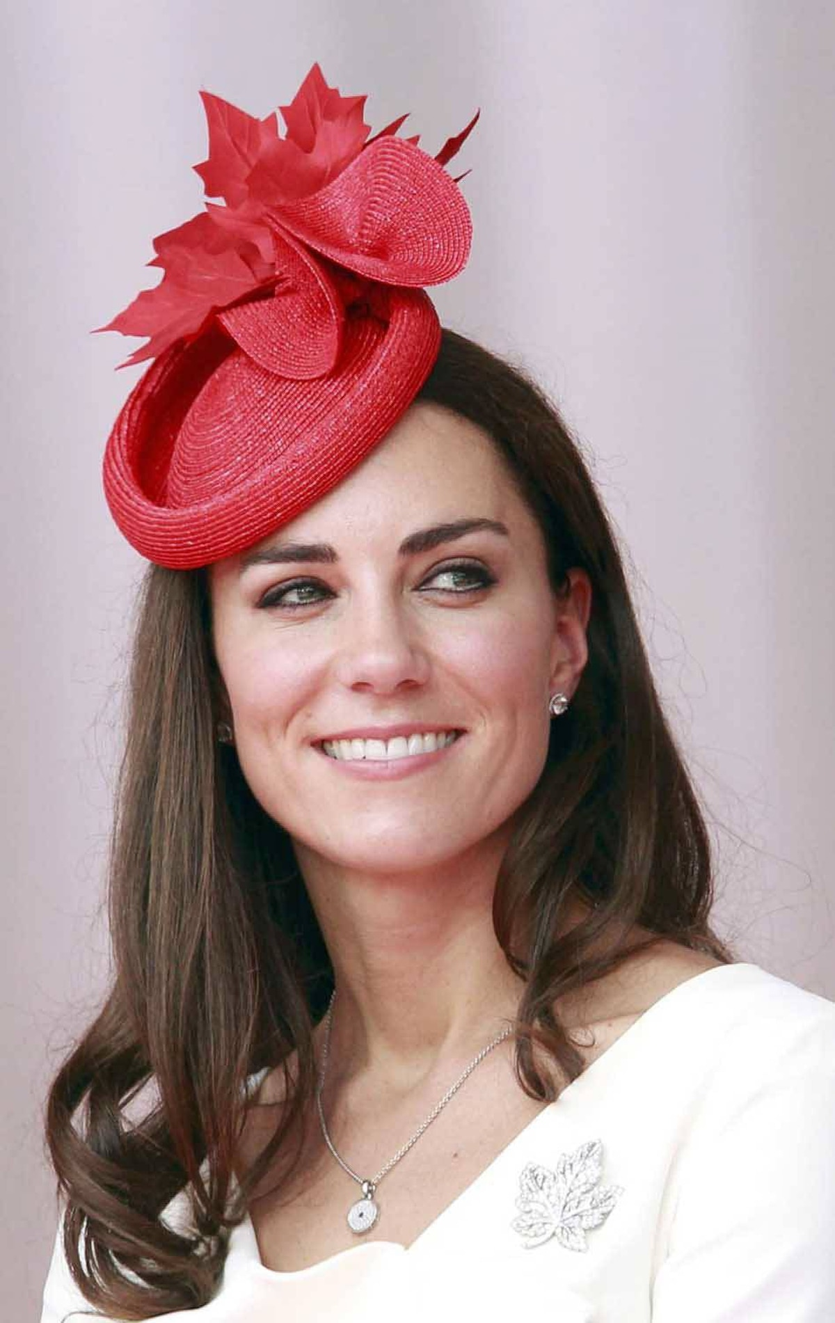 To celebrate Canada Day, Kate shows her spirit by donning a Sylvia Fletcher hat and a maple leaf diamond brooch loaned to her by the Queen. The dress is the same Reiss dress she wore for her official engagement portrait.