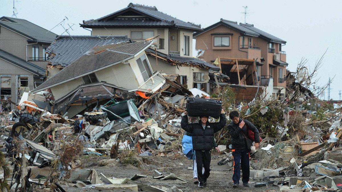 Residents carry belongings from tsunami devastated homes in Natori City, Miyagi prefecture on March 14, 2011.