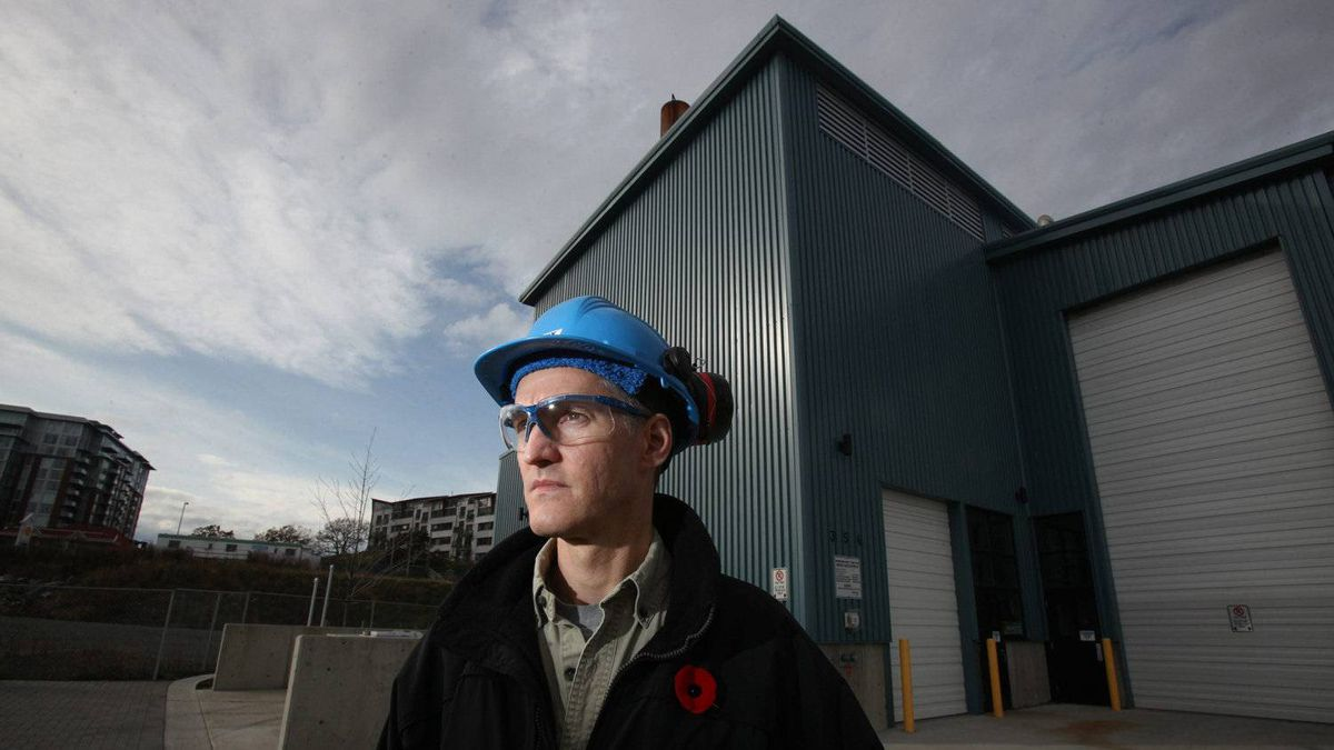 Corix Utilities operator, Terry Balak, stands in front of Canada's first Nexterra gasification system located at Dockside Green Energy Biomass Facility in Victoria.