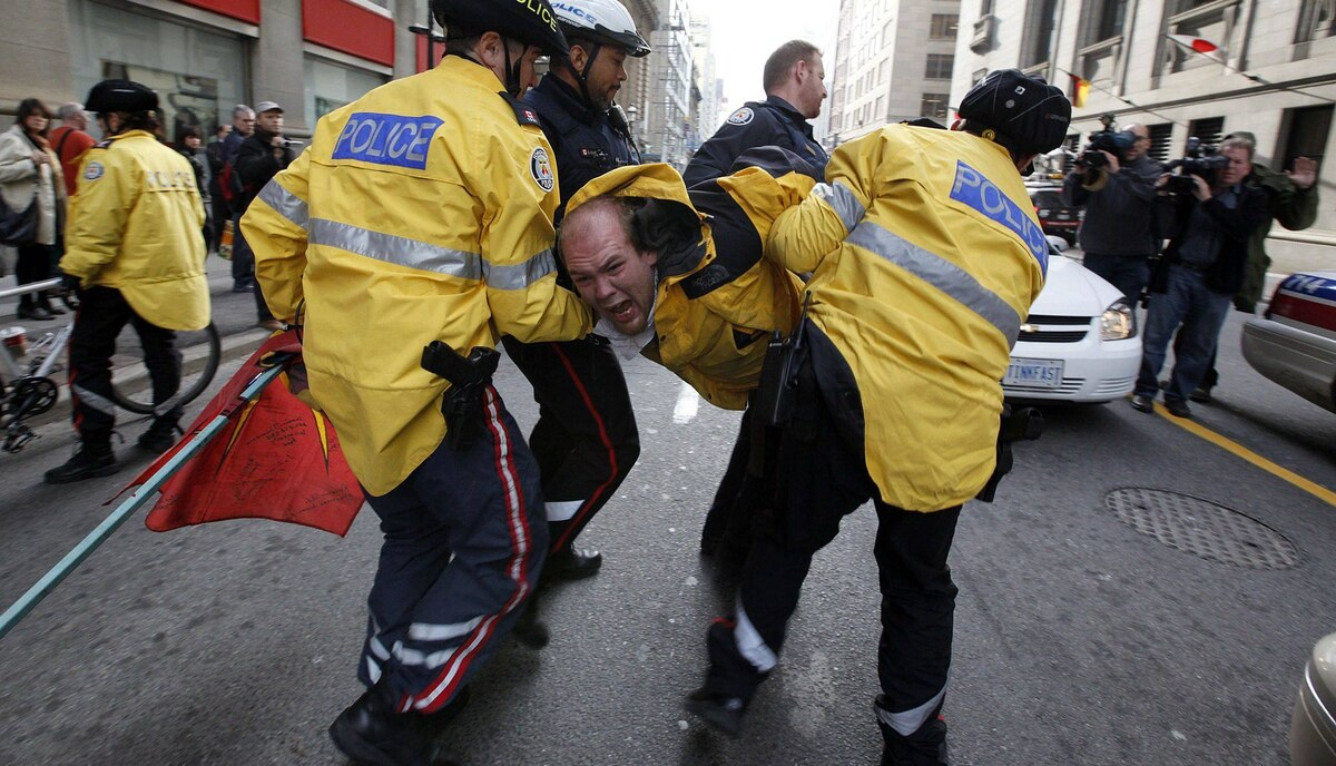 An Occupy Toronto protestor is arrested at King and Yonge Street in Toronto by Toronto Police as a group of protestors made their way back from a protest at Bay and Wellington Street to voice their opinion on the eviction of Occupy Wall Street encampment Tuesday, November 15, 2011.