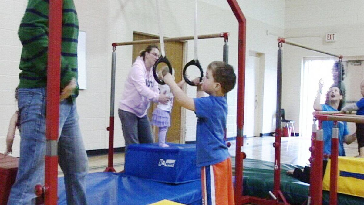 A child prepares to swing on the rings.