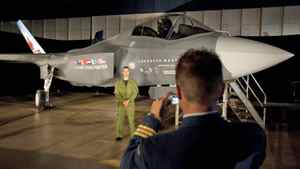 A Canadian Forces pilot has his picture taken in front of a F-35 Joint Strike Fighter model prior to a procurement announcement in Ottawa on July 16, 2010.