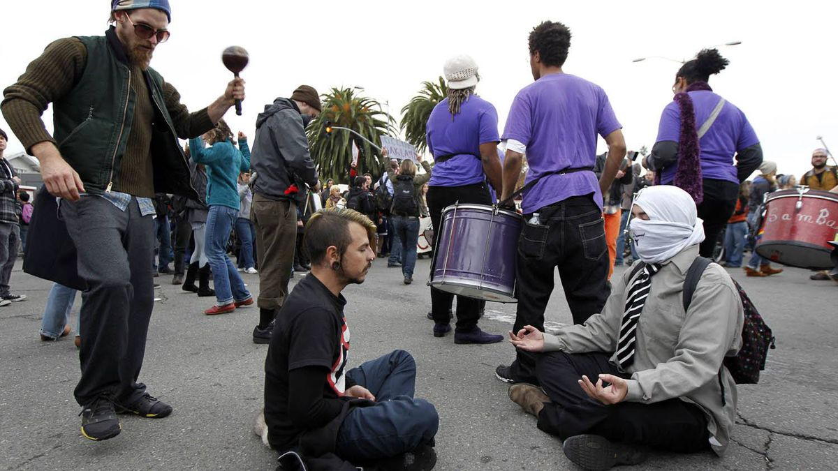 """Demonstrators meditate and dance Nov.19, 2011 in Oakland, Calif. Occupy Oakland protesters, calling for a """"mass day of action,"""" took over a vacant lot in downtown Oakland, claiming it as their new encampment."""