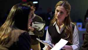 """A woman speaks to a potential employer at the """"Hiring Our Heroes"""" job fair at the Intrepid Sea, Air and Space Museum in New York March 28, 2012."""