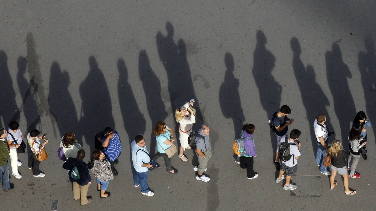 Shadows are cast on the ground as people line up to enter the Eiffel Tower in Paris September 27, 2011.