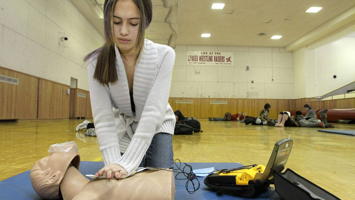 Student Olivia Frierson presses contact pads from an AED machine onto a CPR mannequin during a CPR training class at Shaker Heights High School in Shaker Heights, Ohio on Monday, Jan. 10, 2011.