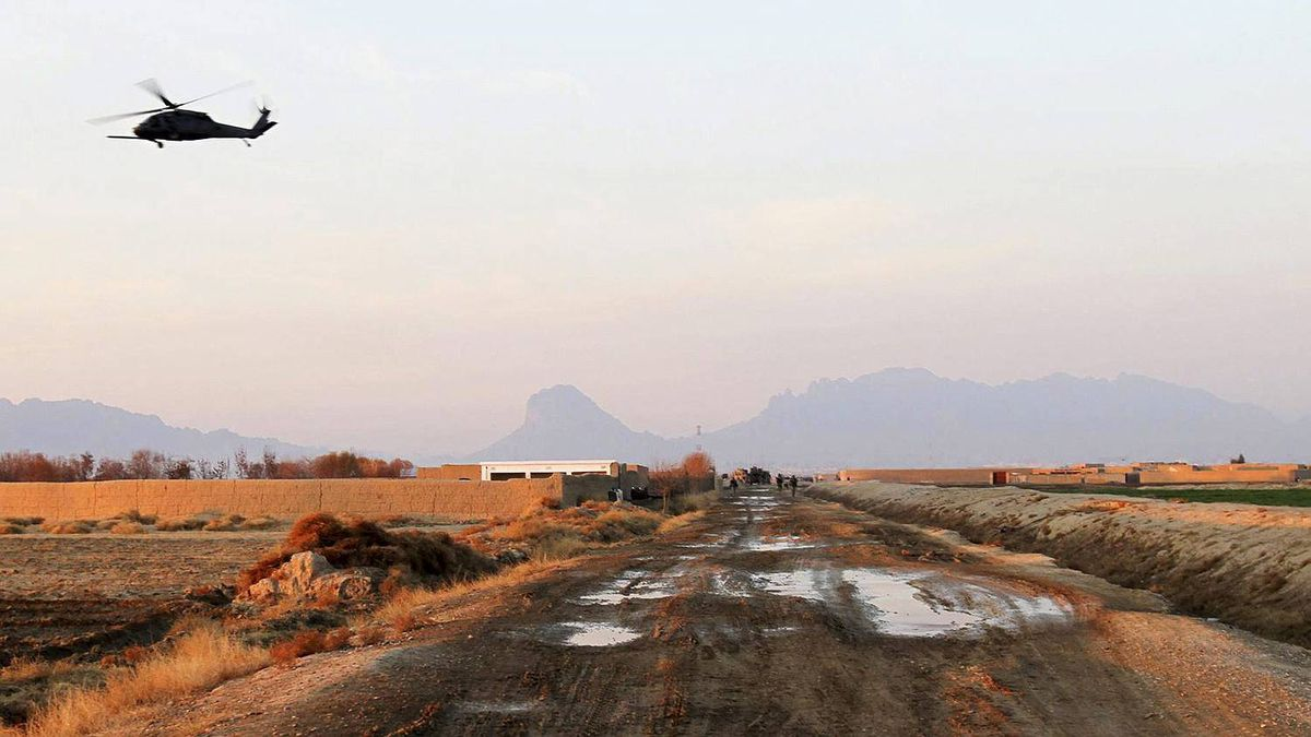 In this image taken on Wed., Dec. 30, 2009, a helicopter flies over the road on which the armored vehicle was hit by the bomb while on a Wednesday afternoon patrol south of Kandahar city.