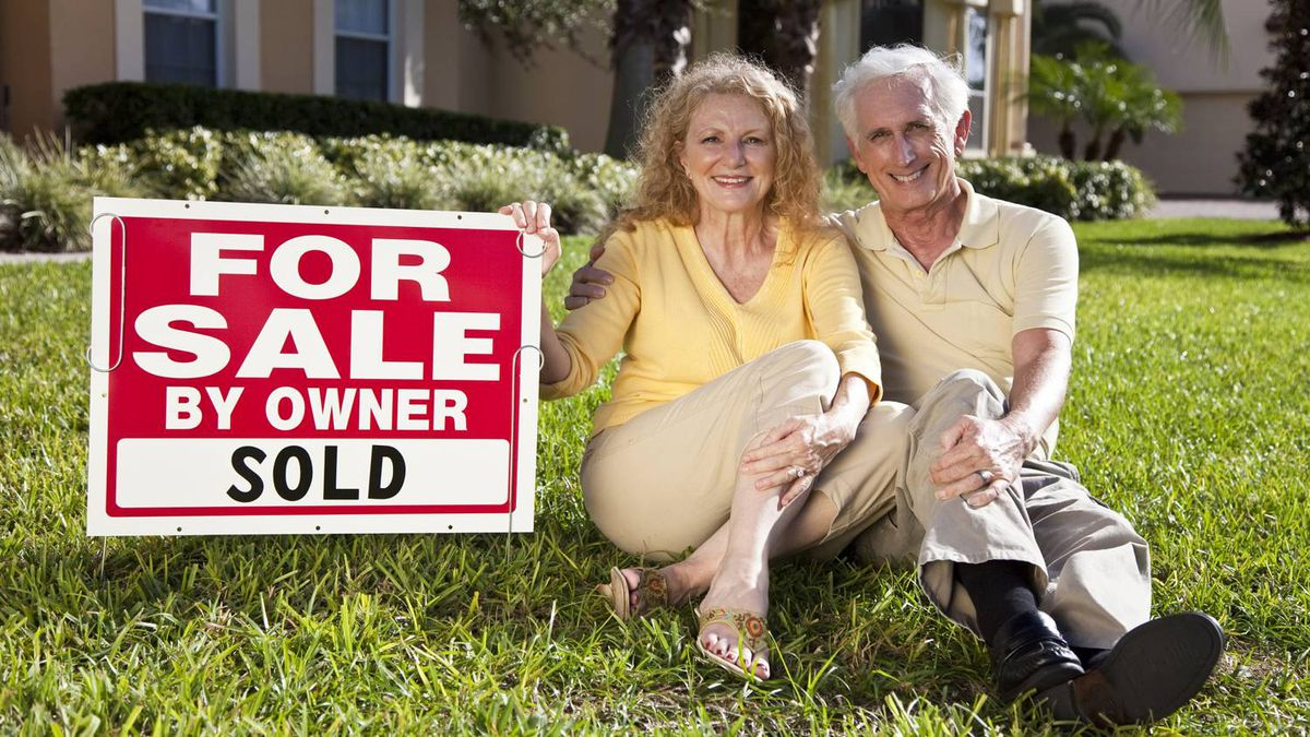 Happy, smiling man and woman senior couple sitting on the grass outside their home ith For Sale Sold by owner sign.
