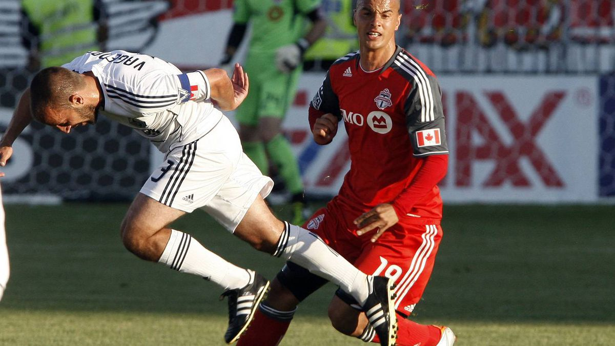 Mikael Yourassowsky #19 of Toronto FC battles with Peter Vagenas #33 of Vancouver Whitecaps FC during MLS action at BMO Field June 29, 2011 in Toronto.
