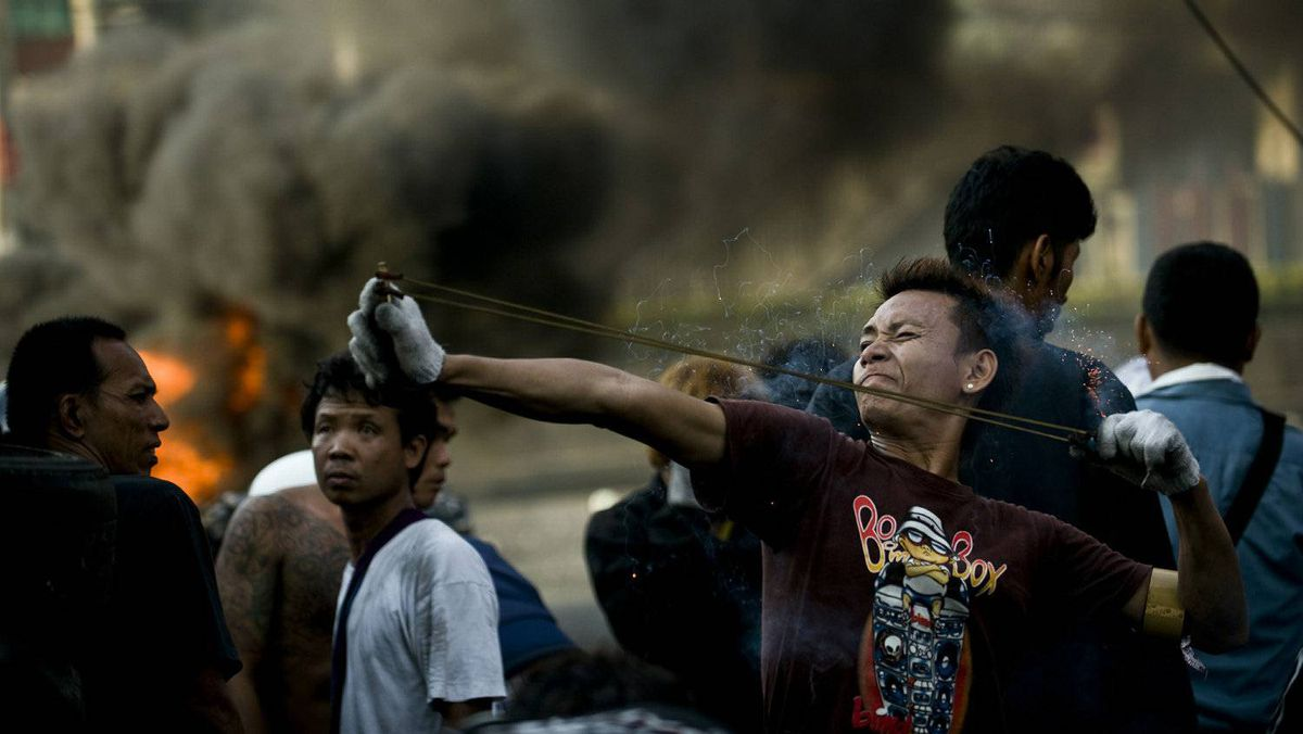 A Thai demonstrator uses a slingshot to launch a firecracker towards army positions in downtown Bangkok on May 18, 2010.