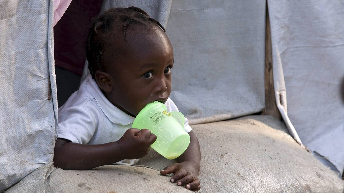 A child living in the muddy hillside camp, Pentionvile Golf Course Camp for Displaced Persons in Port-au-Prince, Haiti, one year after the earthquake rocked the country.