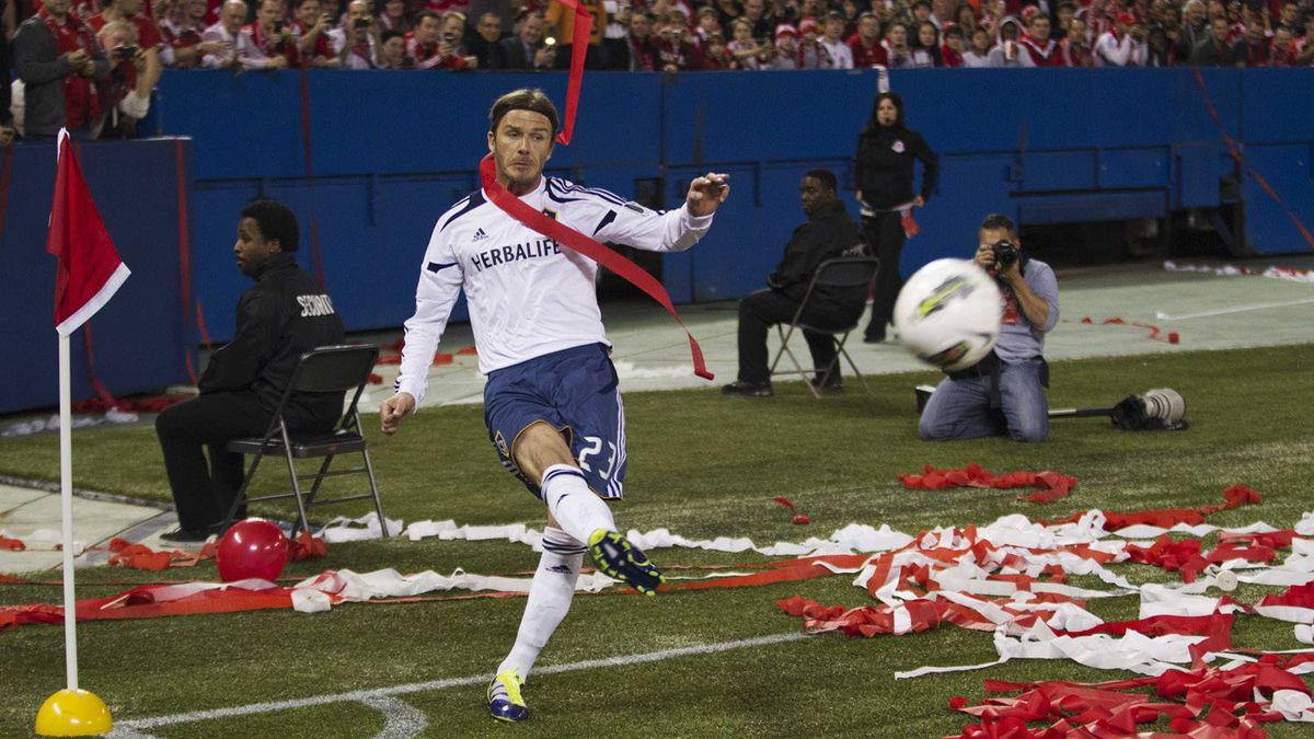 Beckham kicks his corner kick draped in a streamer thrown from the crowd.