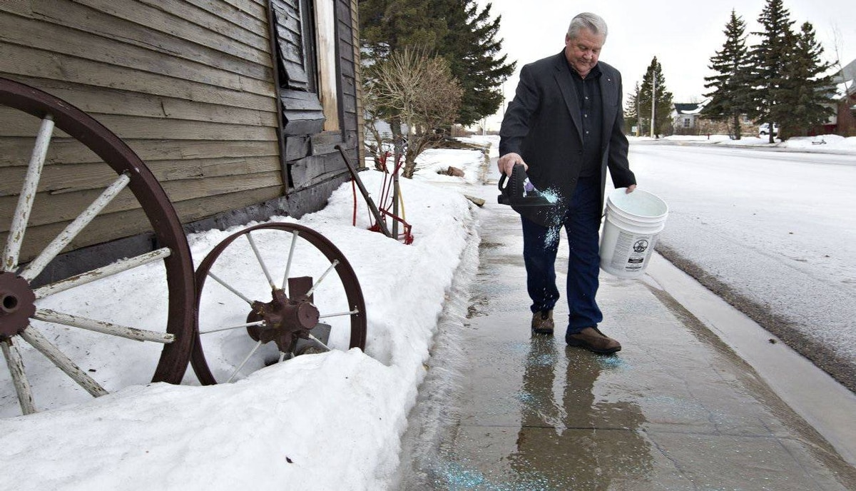 Mayor of Chipman Jim Palmer takes over town foreman duties for the day and salts the sidewalk.