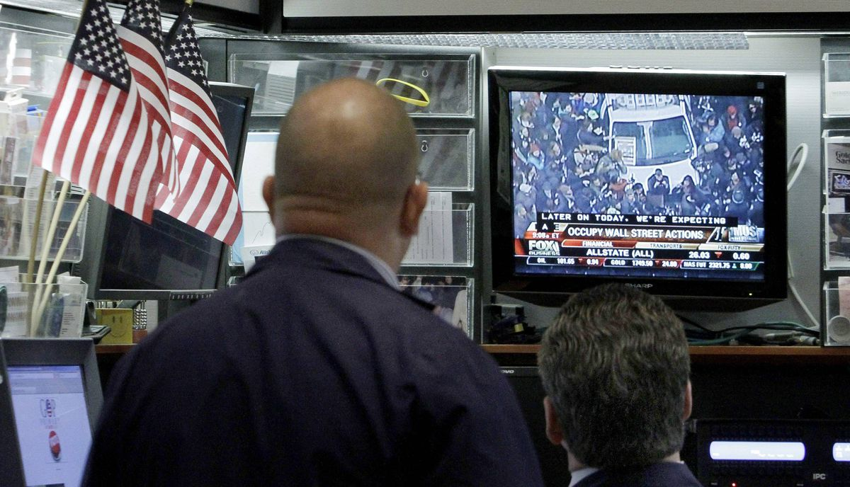 Traders on the floor of the New York Stock Exchange watch a television monitor of Occupy Wall Street activities, Thursday, Nov. 17, 2011.