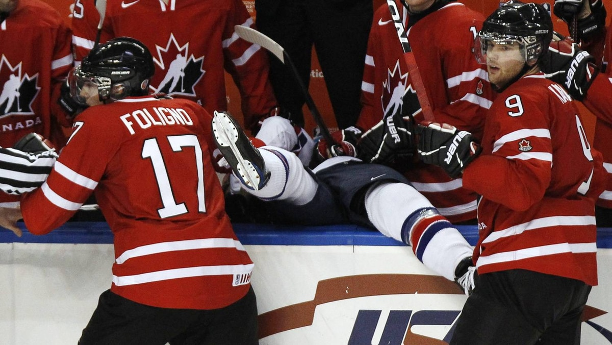 Canada's Marcus Foligno and Zack Kassian put USA's Brock Nelson into Canada's bench during the third period.