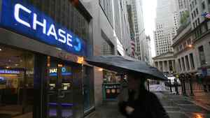 A woman passes a branch of Chase Bank in New York's financial district.