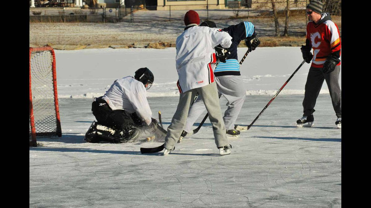 A goalie stops the puck during a game of hockey on a community pond in Calgary, AB.