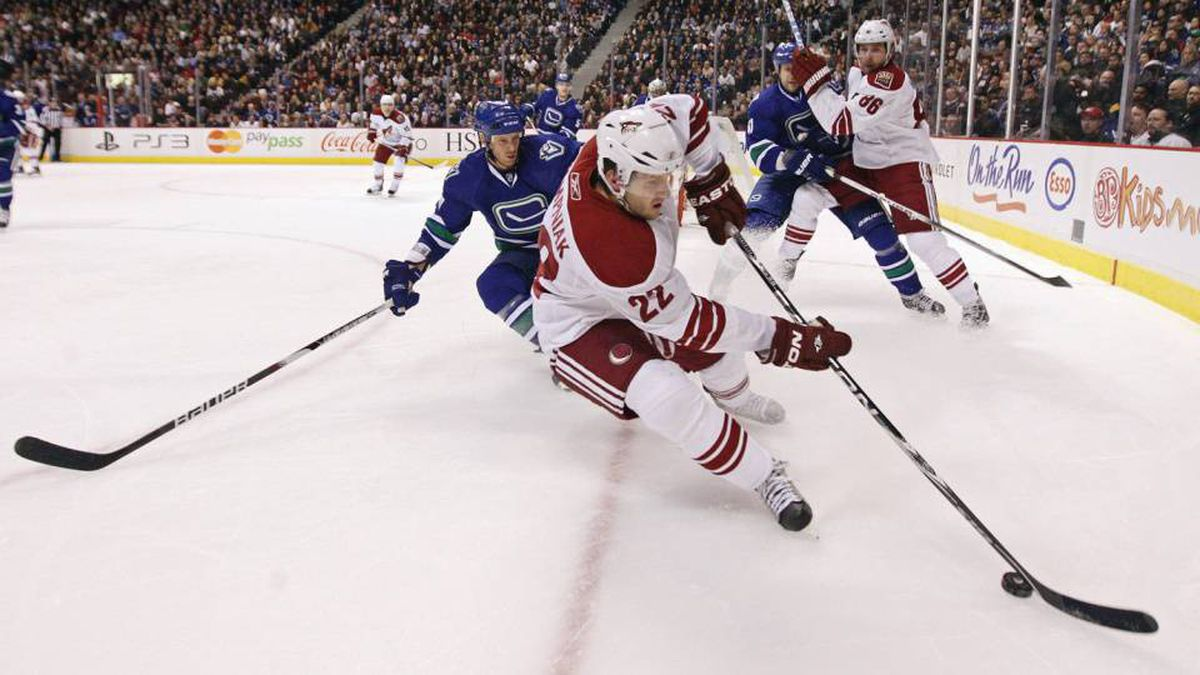 Phoenix Coyotes' Lee Stempniak, 22, plays the puck while being chased by Vancouver Canucks' Ryan Johnson, left, during first period NHL action in Vancouver, B.C., on Tuesday March 30, 2010.