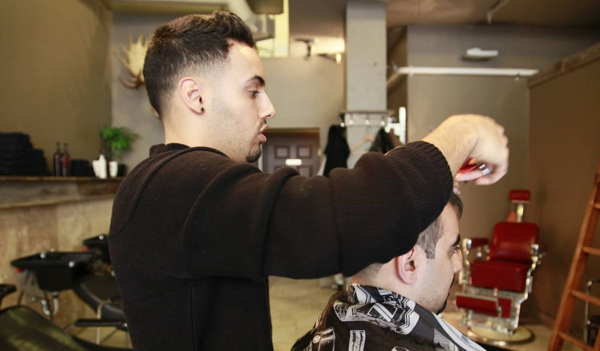 Stylist at Mankind Grooming Studio for men gives a client an Alpha Male haircut