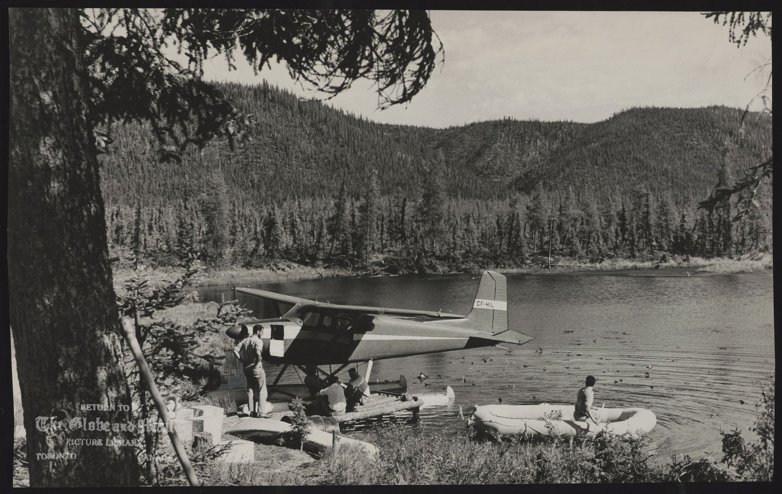 YUKON L.F. The midnight sun lights up this Yukon panorama of lake and trees and the aircraft that carried Bruce West to the busy drilling camp of Eagle Lake where men are probing thousands of feet below the permafrost for oil. This is a camp on Palmer Lake where West landed shortly before he had to transfer to a helicopter.