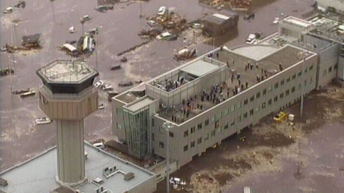 A screen grab taken from news footage by Japanese public broadcaster NHK shows people standing on the roof of the flooded airport and its tower control in Sendai.