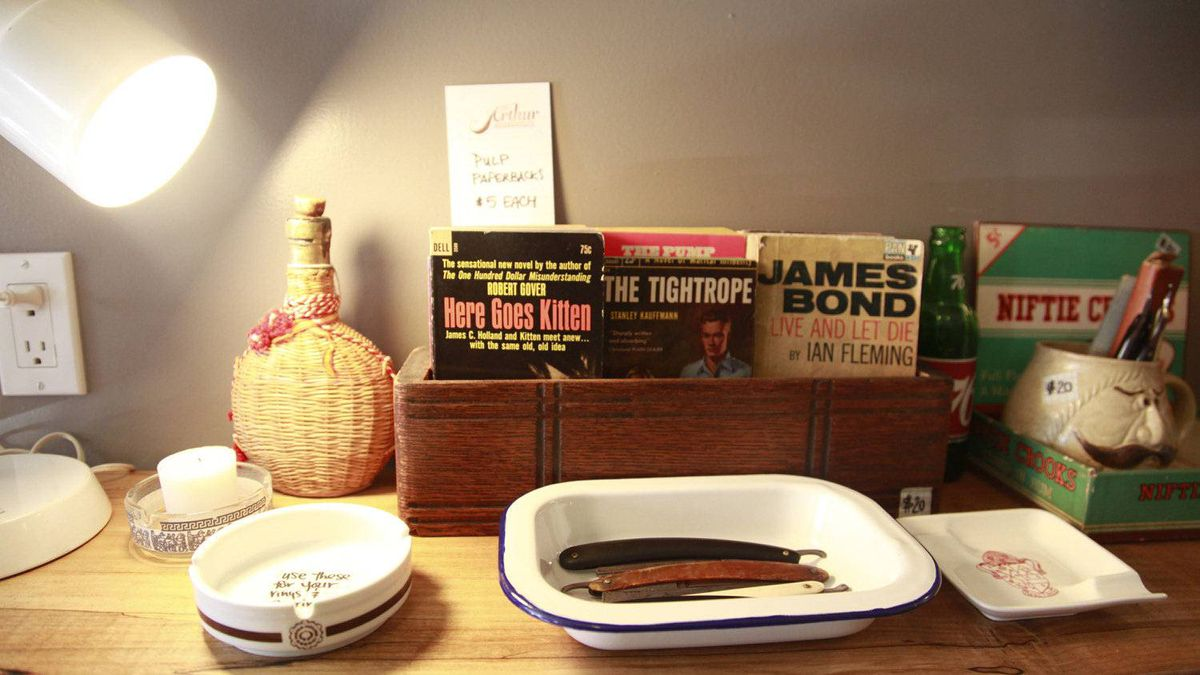 A box of vintage novels compete for attention with an ashtray and straight-razors at the Arthur vintage decor shop in Toronto, Ontario