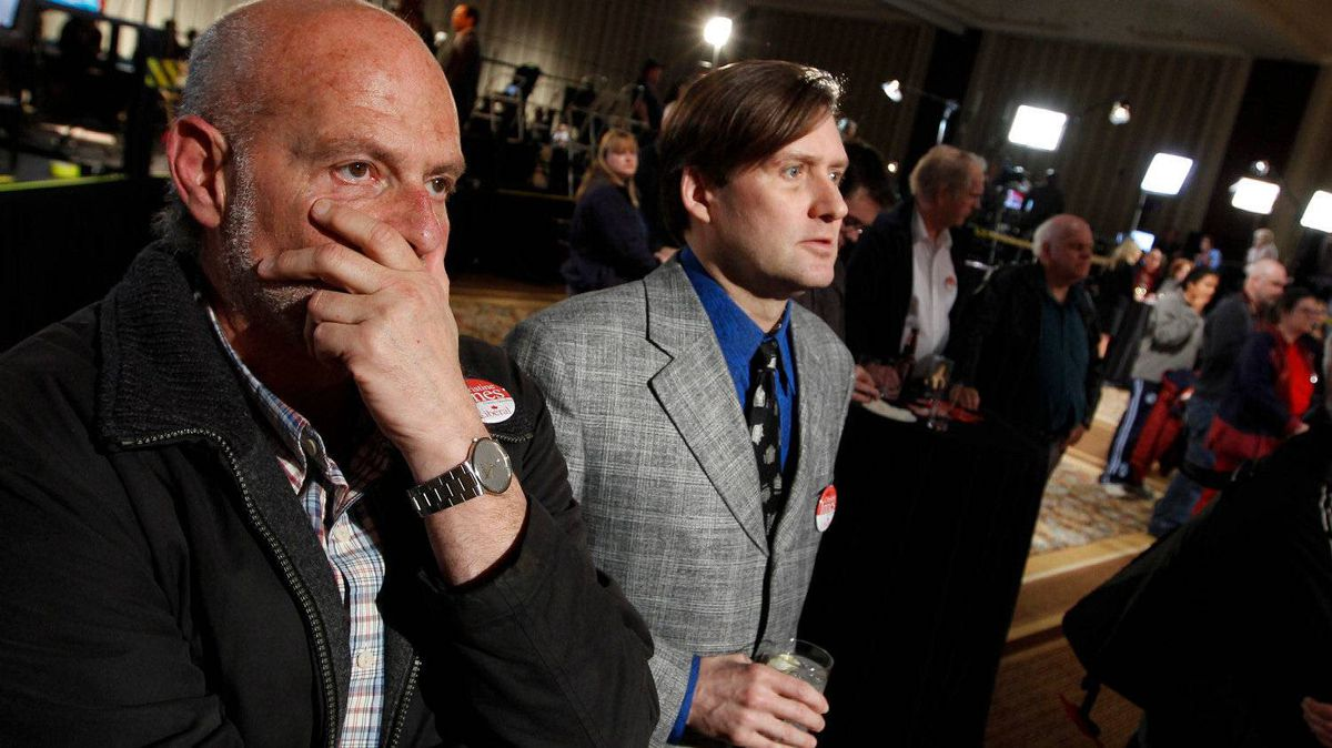 Supporters, Robb Collis, left, and Rick Martin look on as the results come in, saying it looks dire for the Liberals.
