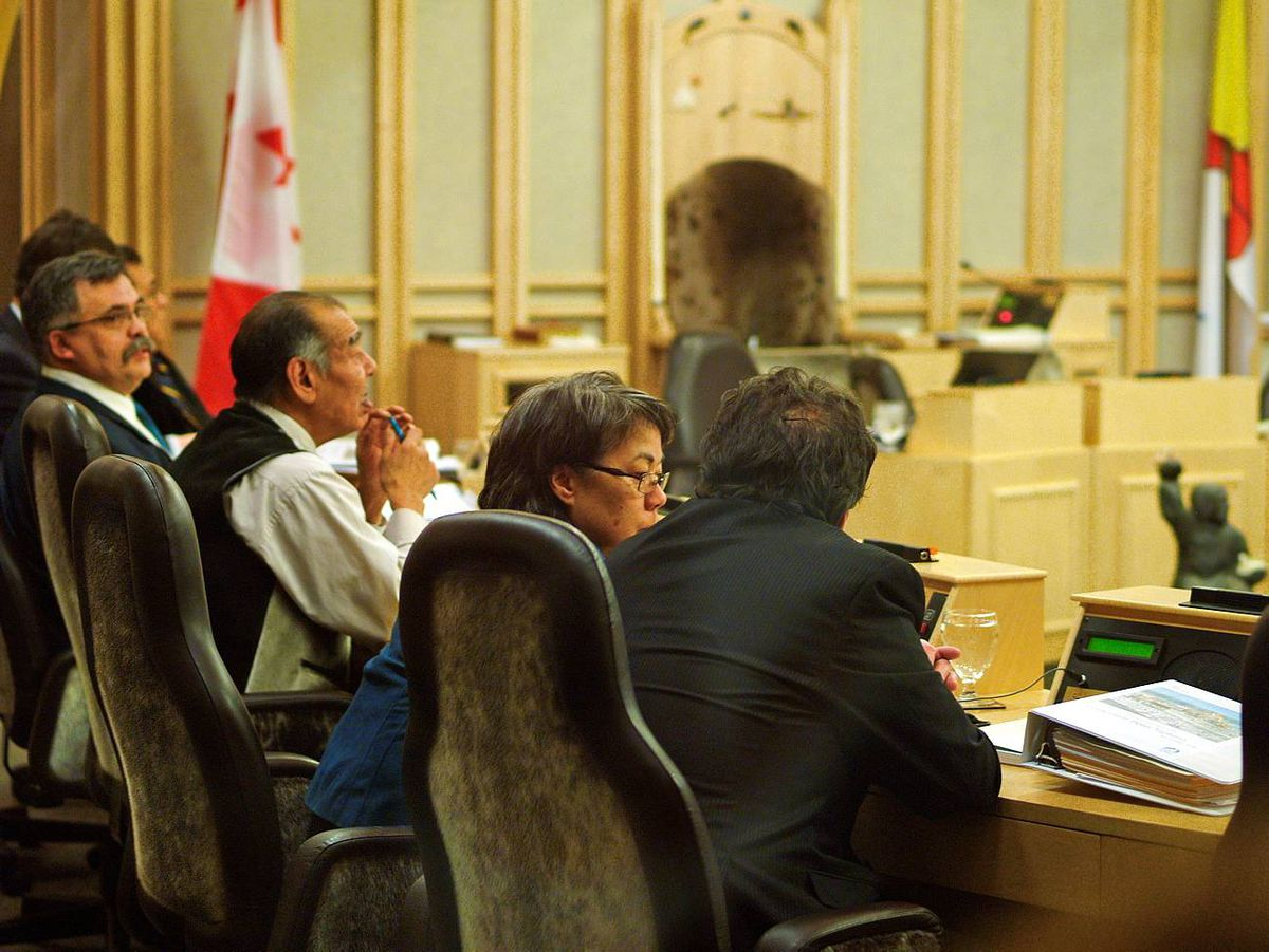 Nunavut Premier Eva Aariak speaks with economic development minister Peter Taptuna, rights, before the start of a sitting of the Nunavut Legislative Assembly, Dec. 7, 2009. The seats covers and side covers under the arms are sealskin.