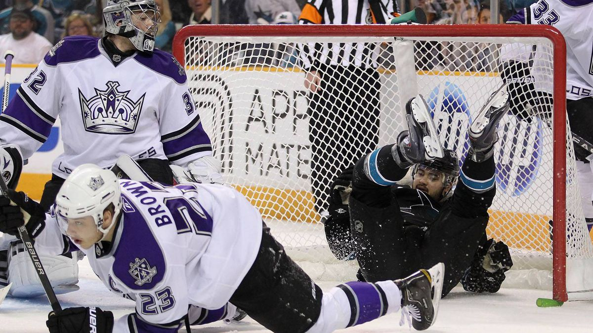 Devin Setoguchi #16 of the San Jose Sharks slides in to the goal after being hit by Dustin Brown #23 of the Los Angeles Kings. The Kings won 3-1. (Photo by Ezra Shaw/Getty Images)