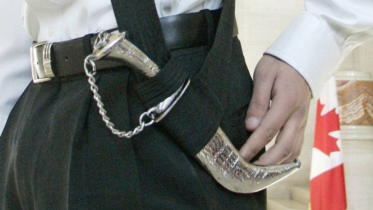 A Montreal teenager displays his kirpan while waiting for a decision from the Supreme Court of Canada in Ottawa on March 2, 2006.