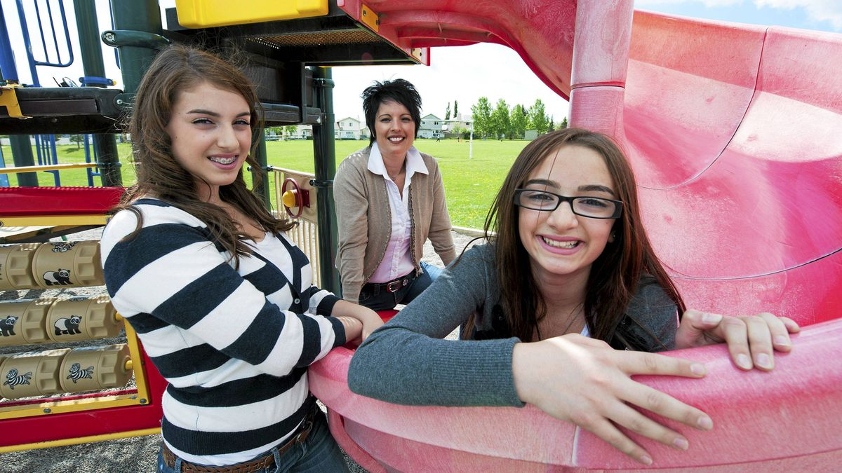Carla Mosca with her daughters Lexi (L) 13 and Giulianna 10 at the school playground in Calgary, Alberta, June 12, 2011.