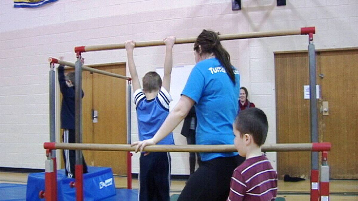 Children in a Kinder Kids class perform with their coach on the uneven bars.